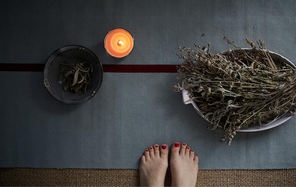Tapis de yoga, bougie et bols d'herbes.