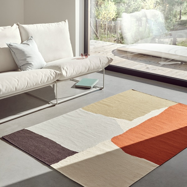 Tapis TVINGSTRUP tissé à la main sur le sol en béton gris d'un séjour moderne.