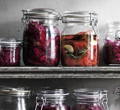 Tarros de vidro nun estante cheos con col en vinagre e pementos vermellos.