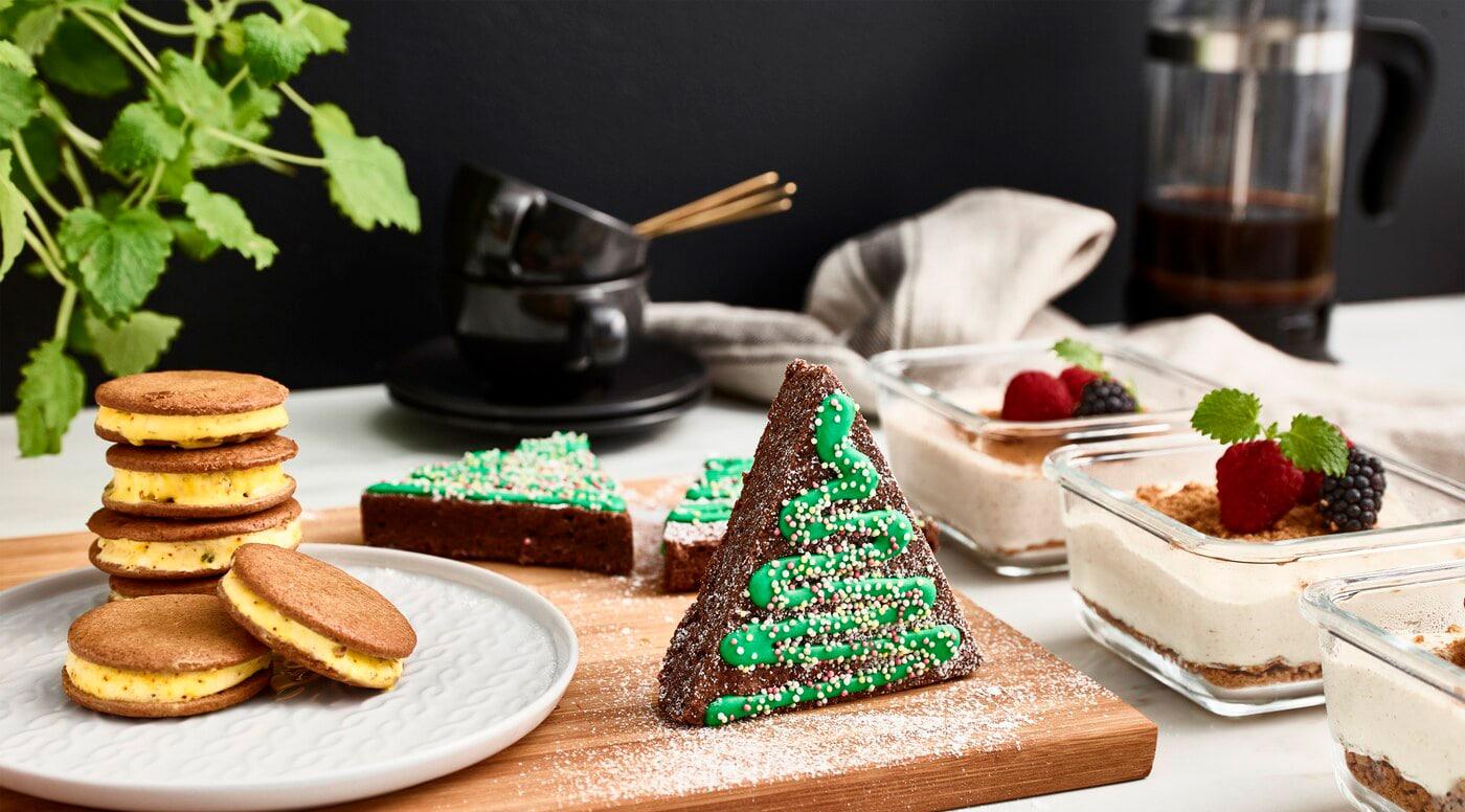 Tarta de queso, galletas de jengibre, pasteles de chocolate decorados en fomra de abetos, tazas y una jarra de café sobre una encimera.