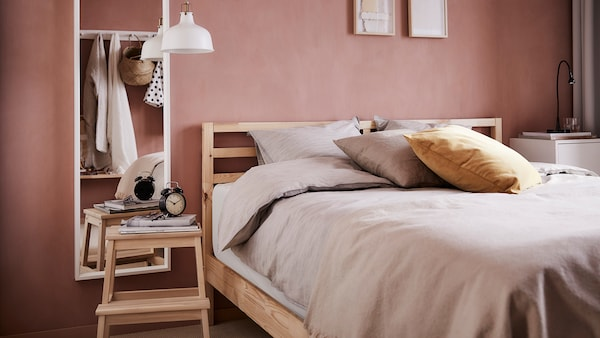 TARVA Bed frame dressed with a duvet and cushions with a step stool and mirror on the side.