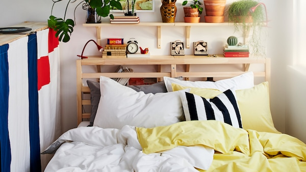 TARVA bed frame dressed with white and pale yellow ÄNGSLILJA bed textiles, against a white wall with aspen shelves.