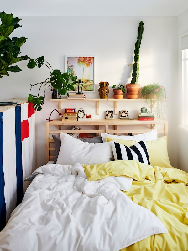 TARVA bed with two sets of ÄNGSLILJA bed linen, one yellow and one white. Plants and decorations on a shelf above the bed.