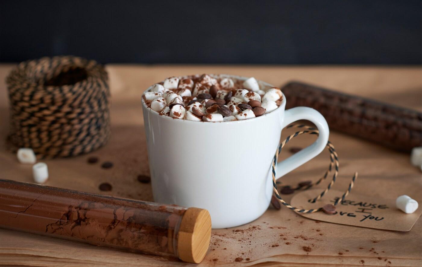Tasse blanche remplie de chocolat chaud, garni de copeaux de chocolat et de mini-marshmallows.