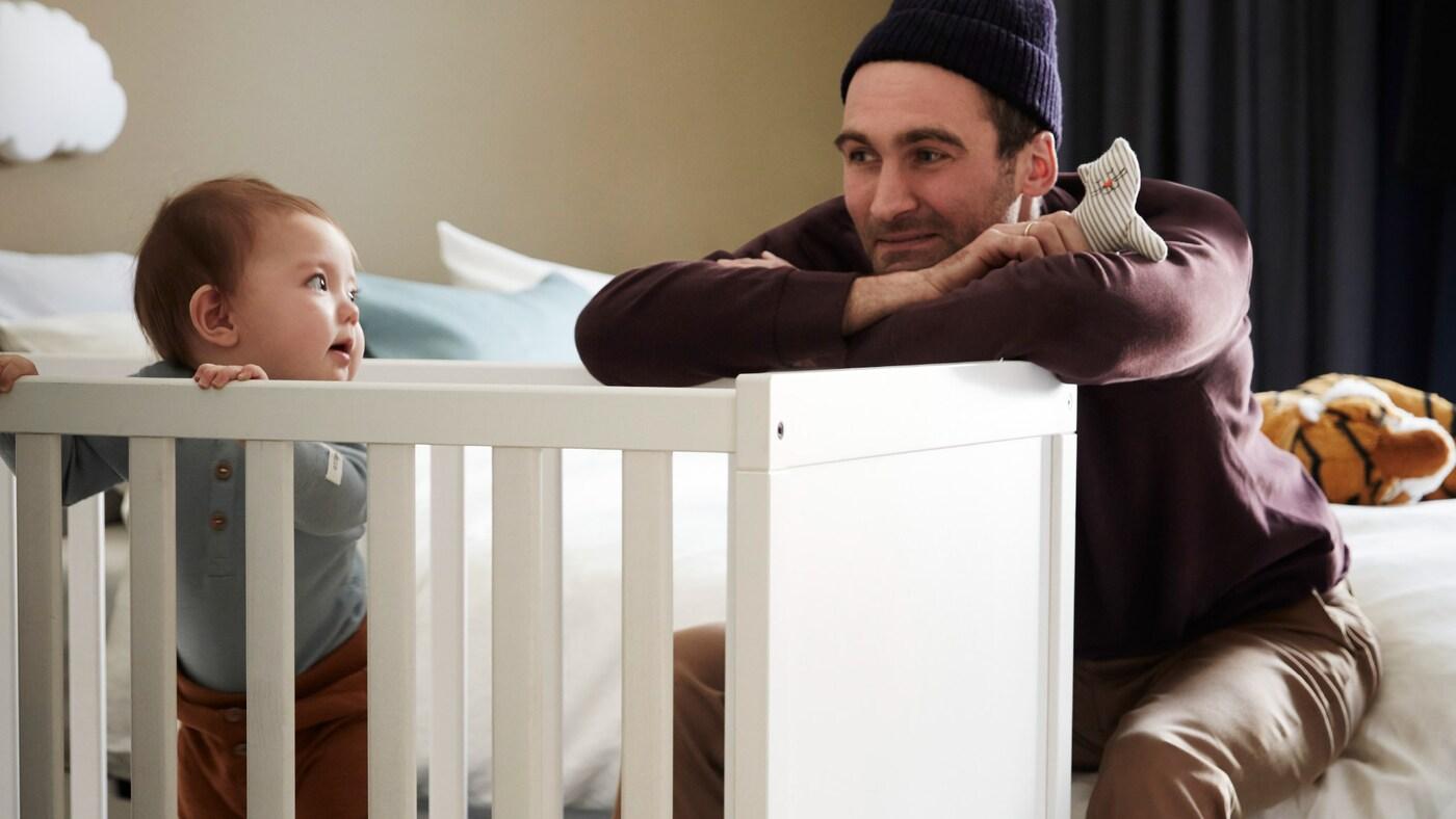 Tată jucându-se un joc cu bebelușul său și cu o jucărie mică din lemn, în timp ce copilul stă în picioare într-un pătuț alb ținându-se de balustradă.