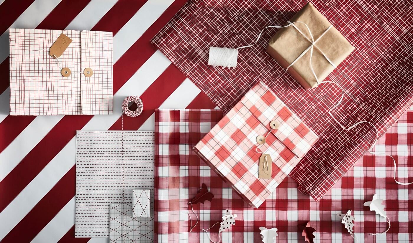 Taula preparada per embolicar regals: paper de diversos colors i estampats, corda, estisores, etiquetes i regals embolicats.