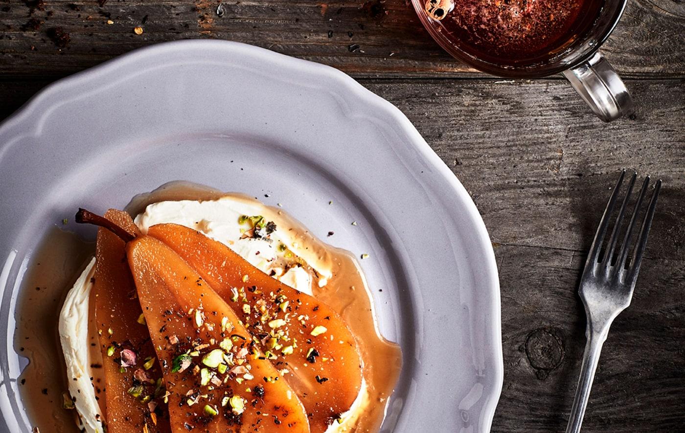 Taulell rústic de fusta amb una ració de postres a base de peres i productes lactis en un plat, una forquilla i una tassa de te al costat.