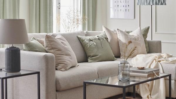 Tavaszra hangolt nappali bézs VIMLE kanapéval, RÖDASK, AINA és SANELA díszpárnahuzatokkal, VITTSJÖ asztallal és SNÖBYAR lámpával.