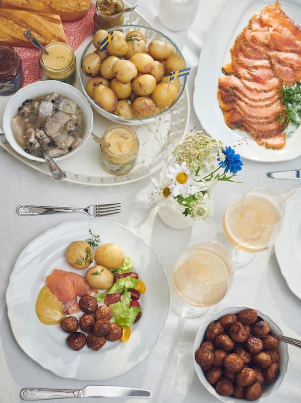 Tavola con piatti, posate ÄTBART, salmone marinato su un piatto, polpette in una ciotola e aringhe su un vassoio ROMANTISK - IKEA