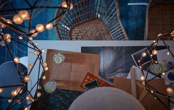 Tavolo con strumenti astronomici e sedie di vimini su un tappeto blu e fili di luce a LED - IKEA
