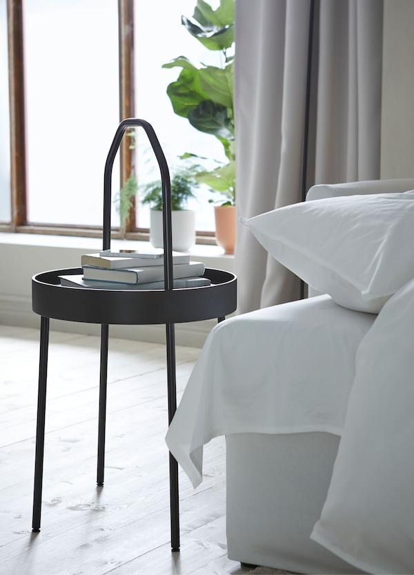 طاولة جانبية مستديرة سوداء BURVIK من ايكيا بيد رفيعة خفيفة في غرفة جلوس.
