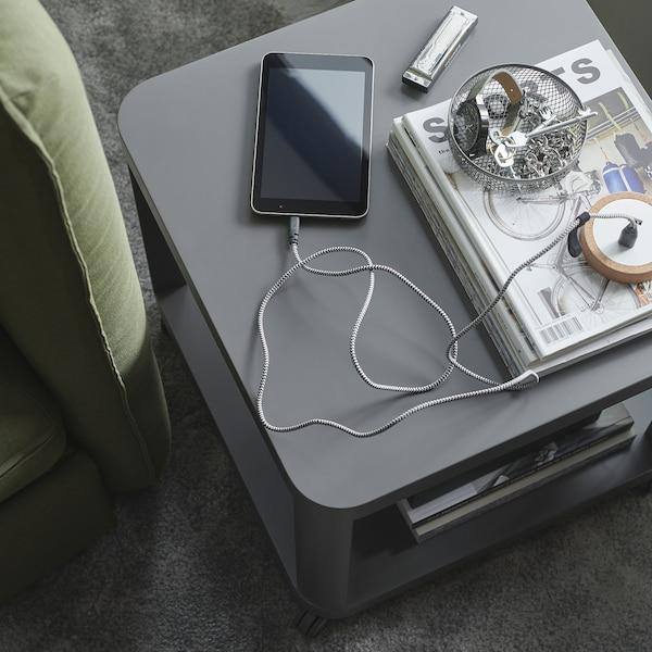 طاولة جانبية رمادية، وإناء شبكي بداخله مفاتيح وهاتف ذكي يتم شحنه بواسطة كابل LILLHULT مغلّف بالقماش.