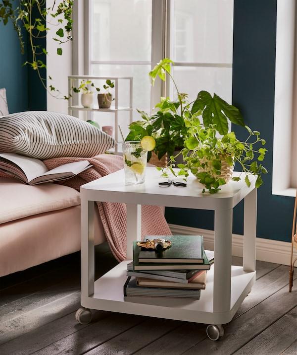 طاولة جانبية شكل مكعب مستويين على عجلات - مع كتب أسفلها، ونباتات وكوب من أعلى - بجوار أريكة استرخاء.