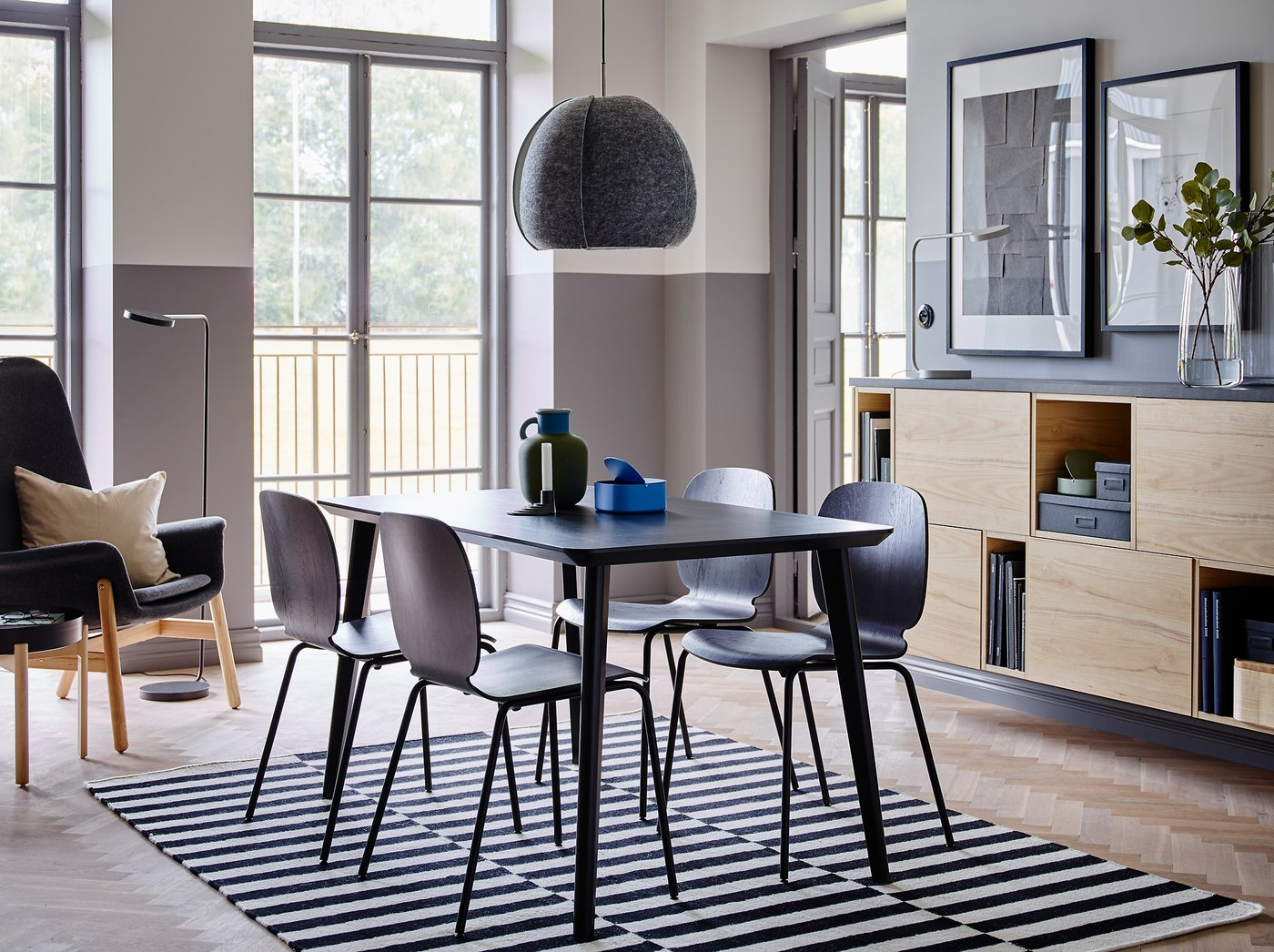 طاولة LISABO سهلة التركيب وكراسي SVENBERTIL السوداء تضفي تشكيلة أنيقة في منتصف الغرفة مع جدران نصفها رمادي ونصفها أبيض وتخزين مغلق من خشب الدردار.