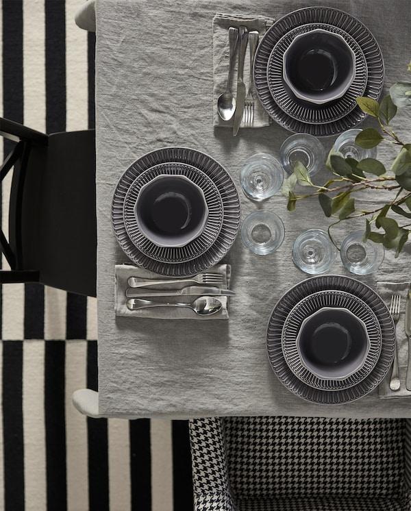 طاولة مع مفرش رمادي ومناديل ورقية رمادية وأطباق وسلطانيات من الخزف الرمادي وأدوات تناول طعام من الستنلس ستيل.