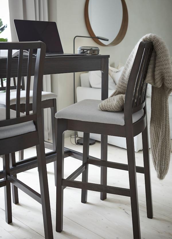 طاولة مرتفعة وكراسي مرتفعة بني داكن EKEDALEN من ايكيا مع وسائد رمادي فاتح، وكمبيوتر مفتوح على الطاولة.