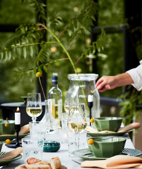 طاولة مُعدة جيدًا لتناول العشاء في الخارج مع أطباق خضراء وكؤوس مشروبات وشموع والكثير غيرها. إظهار الطبيعة.