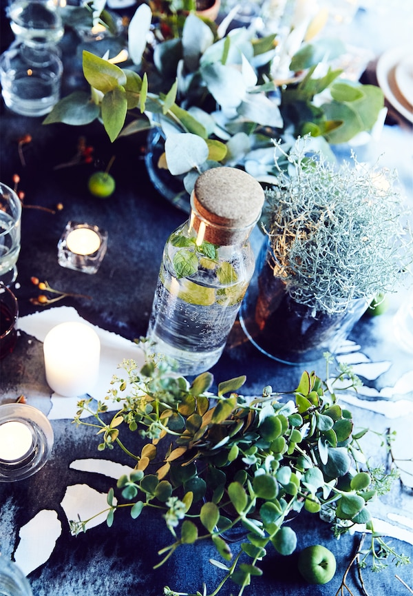 طاولة مزينة بالنباتات الخضراء.