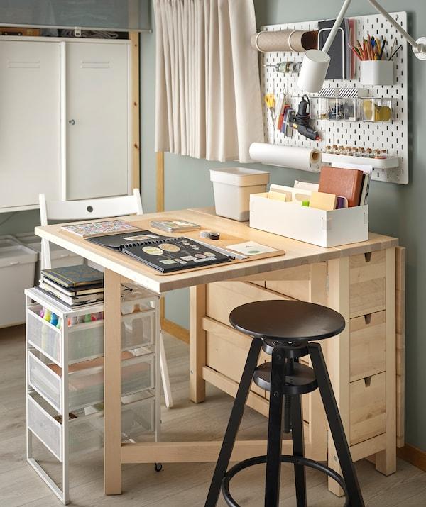 طاولة NORDEN مرتبة لإنشاء القصاصات، منظمة للغاية والإكسسوارات في متناول اليد على طاولة، ولوحة مشابك وفي الأدراج.