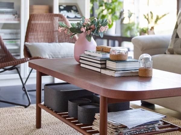 طاولة قهوة مستطيلة بني LISTERBY من ايكيا مستخدمة لتخزين كتب وصناديق على رف سفلي.