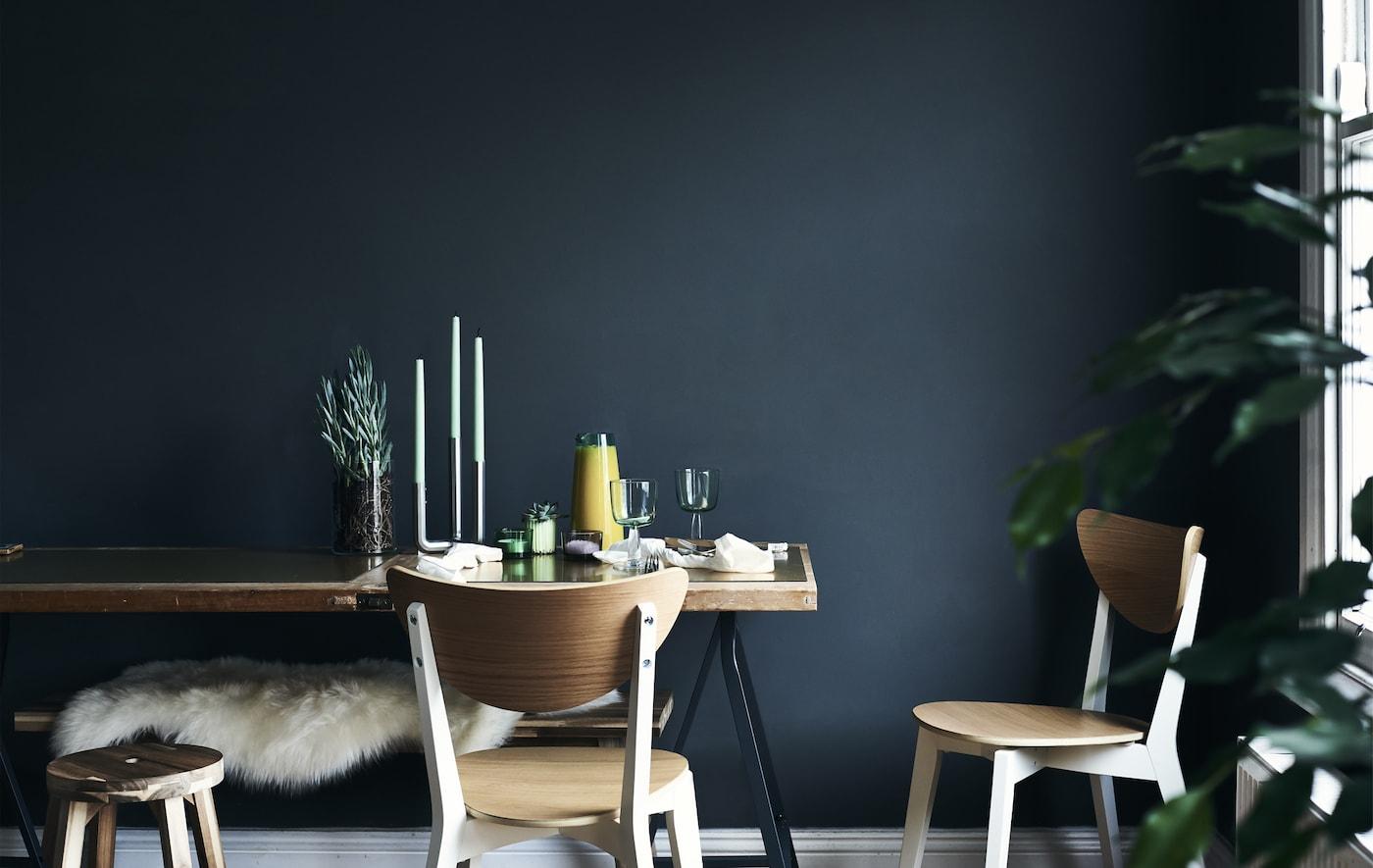 طاولة طعام بمحاذاة حائط أزرق داكن.