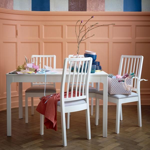 طاولة طعام بيضاء قصيرة مع كراسي لون أبيض.