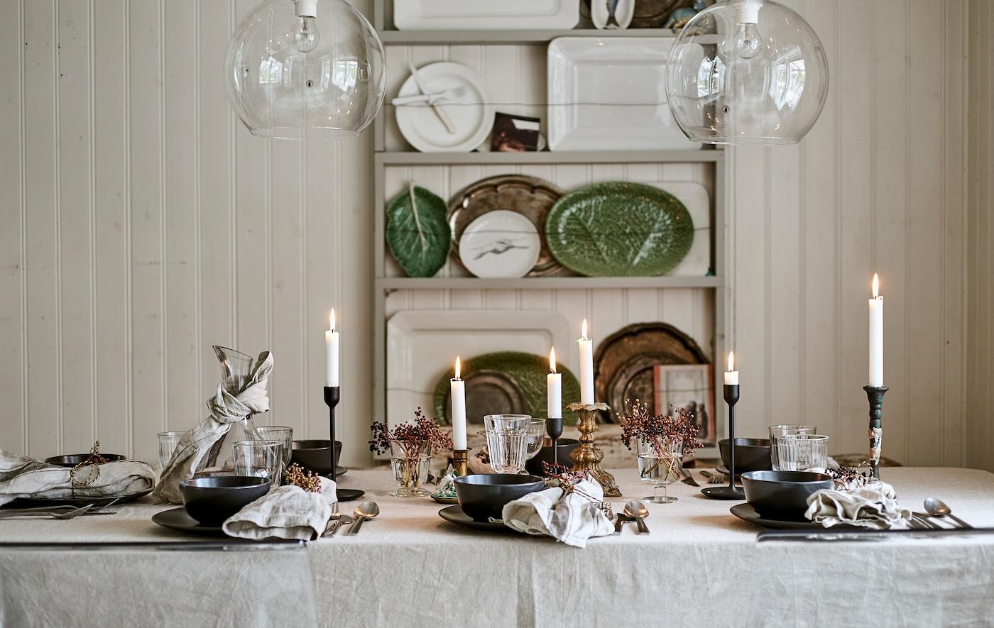 طاولة طعام مخصصة لوجبة احتفالية مع قماش طاولة من الكتان وشموع وأواني زجاجية مع تحديد الأماكن بمناديل مزيّنة.