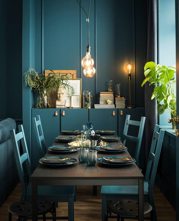 طاولة طعام وكراسي مطلية بشكل مخصص بنفس درجة اللون الأخضر، ومجهزة بأواني الطاولة بلون مشابه.