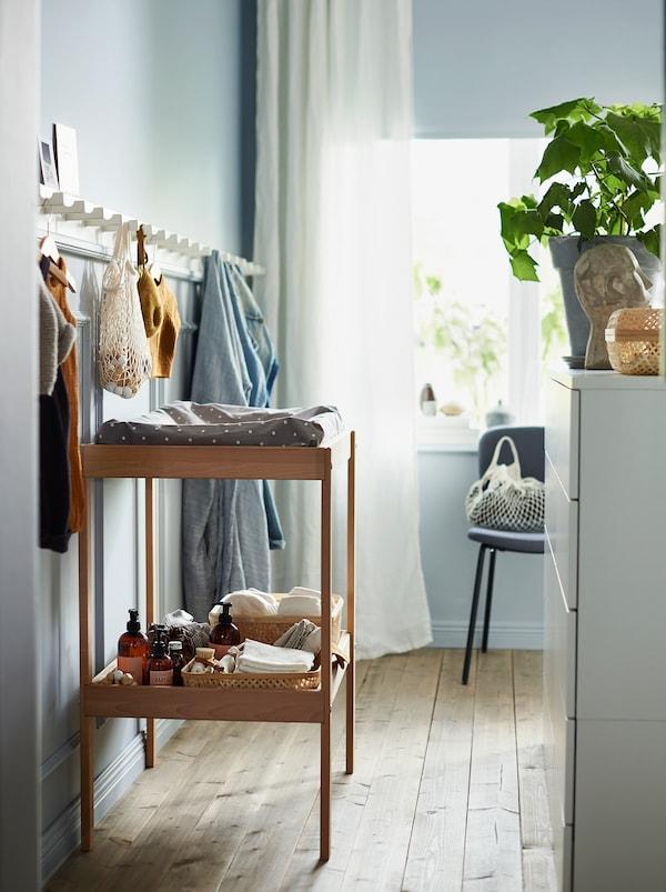 طاولة تغيير خشبية SNIGLAR مع رف تخزين ولوحطويل من الخطافات الخشبية البيضاء على الحائطأعلاه.
