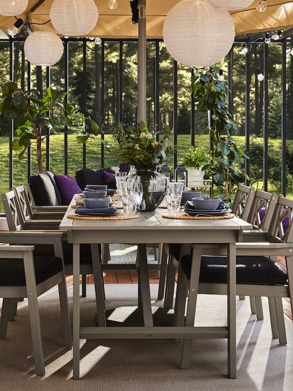 طاولة وستة كراسي مع مسندين للذراعين رمادي للأماكن الخارجية ووسائد مقعد سوداء. الطاولة مجهزة بأواني طعام زرقاء.