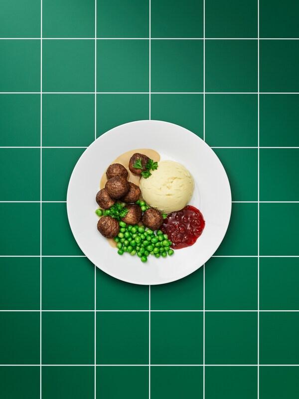 طبق أبيض سادة به كرات اللحم النباتية، وصوص بني، وبطاطس مهروسة، ومربى التوت البري الجبلي، لبازلاء خضراء وغصن بقدونس.