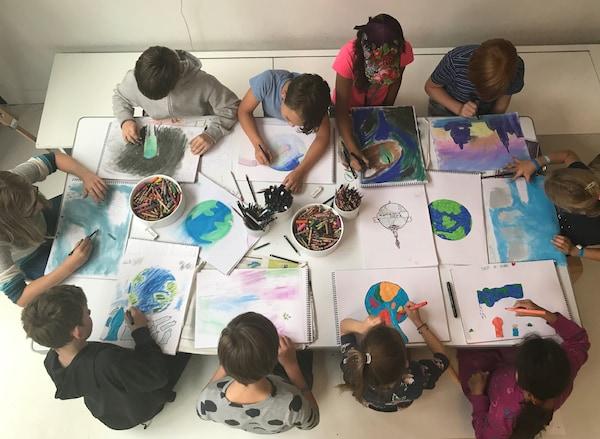 テーブルを囲んで座り、地球の絵を描いている子どもたち。