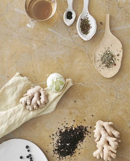 Te-hostoak zeramikazko koilara batean, jengibre-sustraiak eta lima.