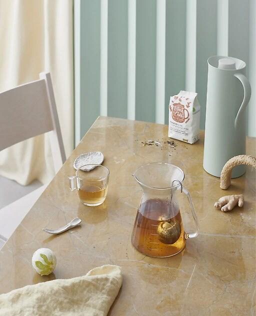 Tea kristalezko teontzi batean eta kikara bat mahaian.