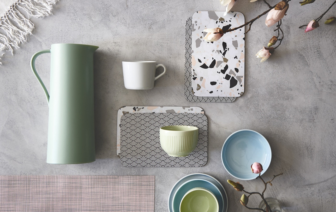 Teacups and trays in pastel colors laid out on concrete.