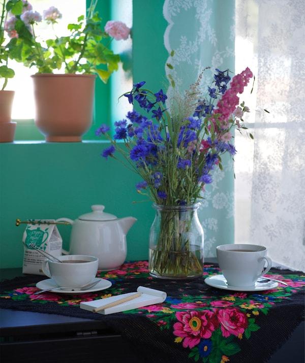Teapot and tea cups beside a flower arrangement in a glass vase.