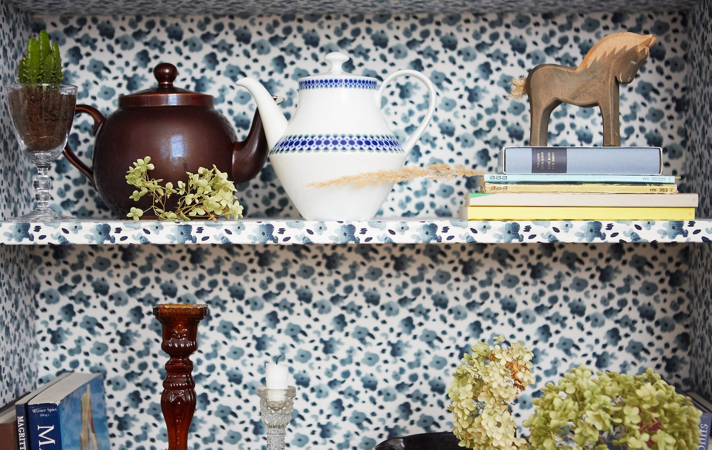 Teapots, books and ornaments on shelves, which are covered with a blue floral fabric.