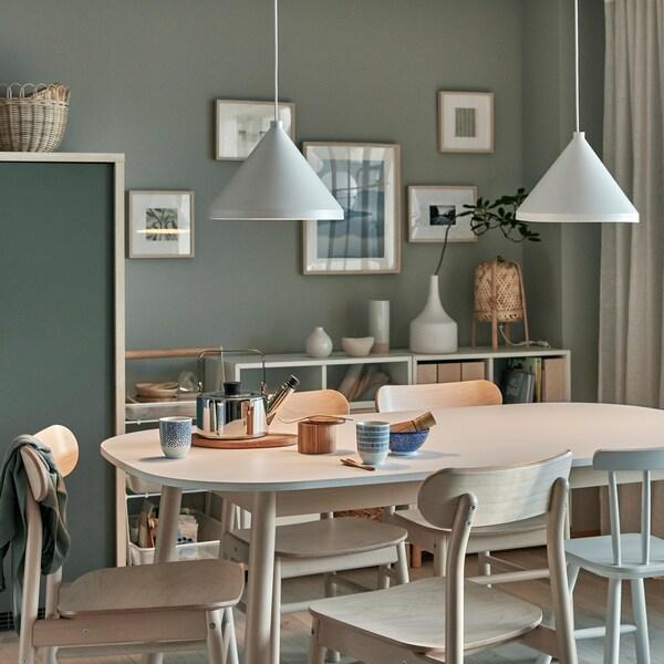 Tee für zwei auf dem Esstisch, über dem zwei NÄVLINGE Hängeleuchten in Weiß sanftes Licht spenden.