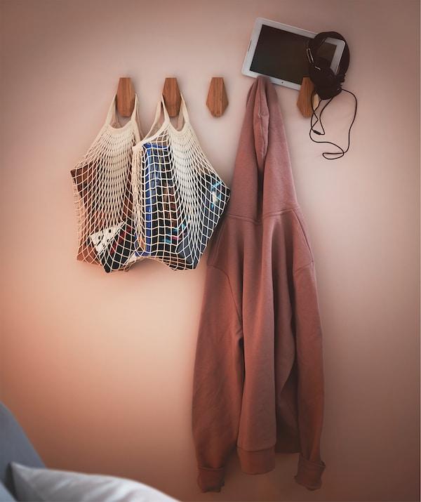 Teil einer Schlafzimmerwand mit mehreren SKUGGIS Haken, denen die KUNGSFORS Einkaufsnetze, ein Hoodie und ein Tablet mit Kopfhörern zu sehen sind.