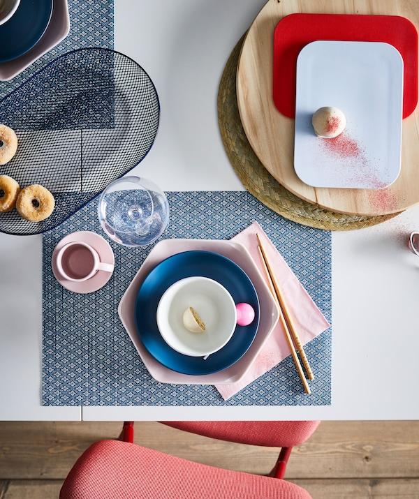 Teil eines Esstisches, u. a. mit einem GALLRA Tischset in Blau, farbenfroh mit anderen Mustern und Formen kombiniert