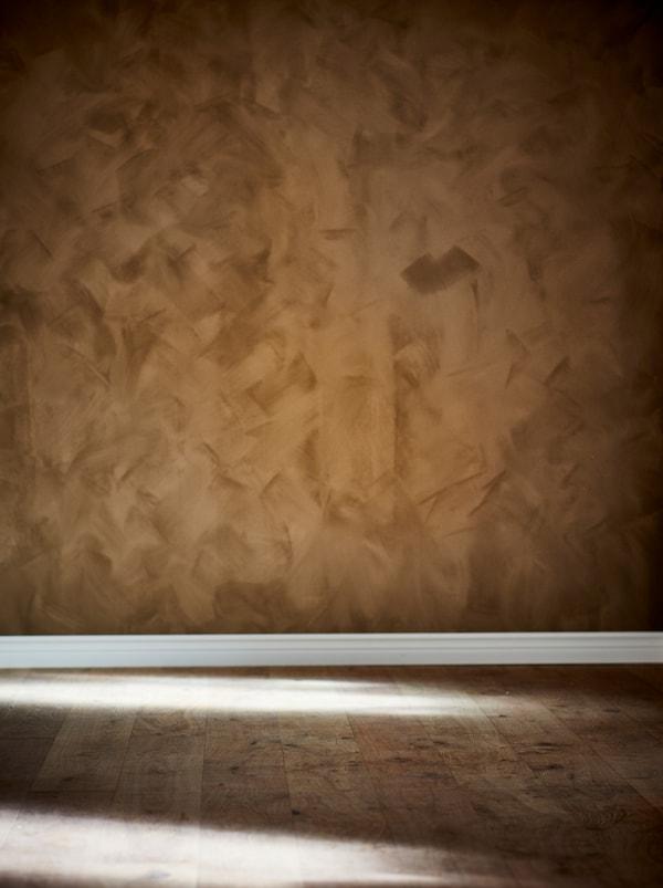 Teil eines leeren Raumes mit Holzboden. Die Wand ist in einem satten Braunton gestrichen, der an Wildleder erinnert.