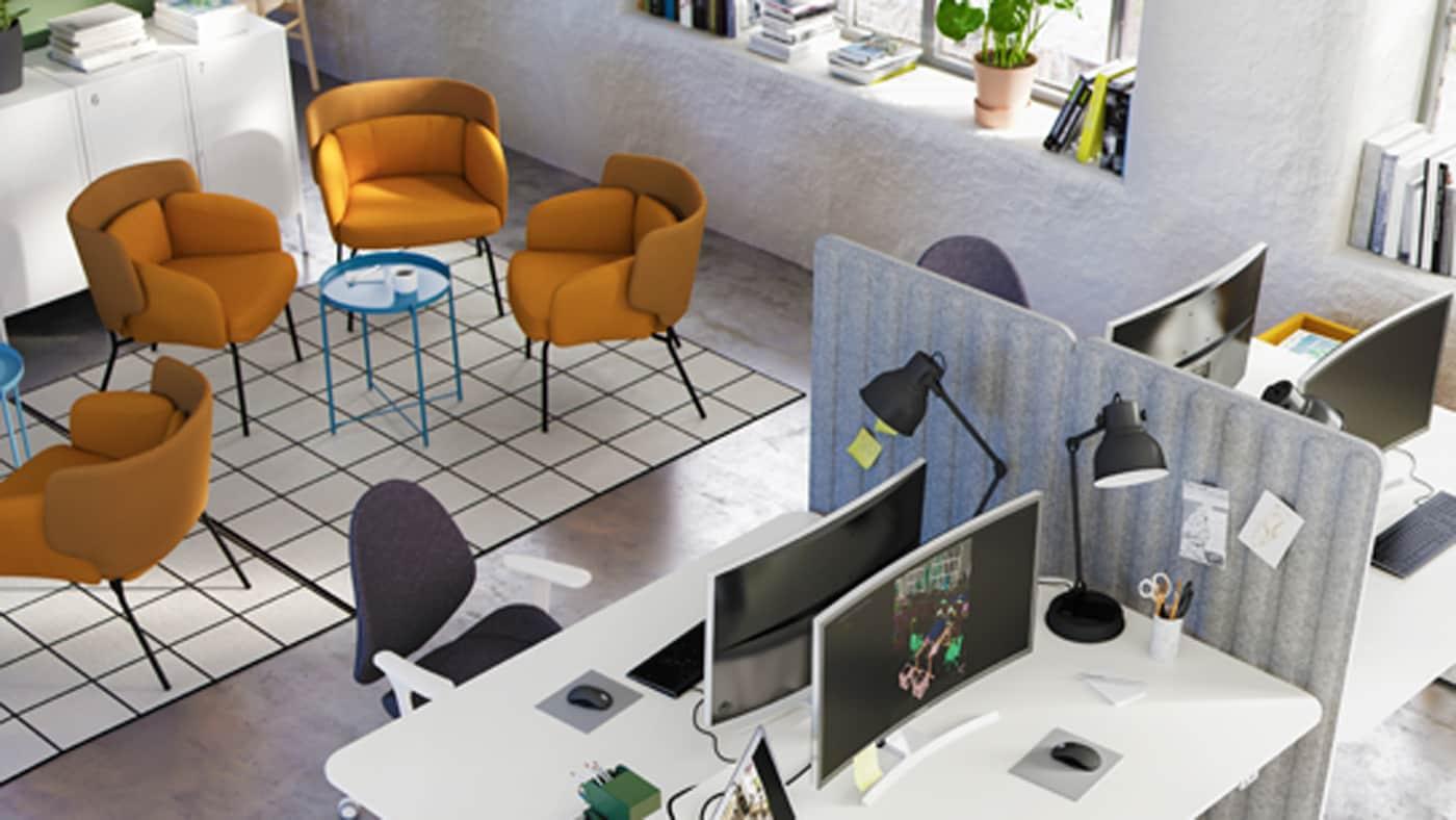 Teil eines Raums mit Bereichen zum Entspannen: Sessel und Couchtisch, ein Bereich mit Arbeitstischen, Drehstühlen und Aufbewahrung.