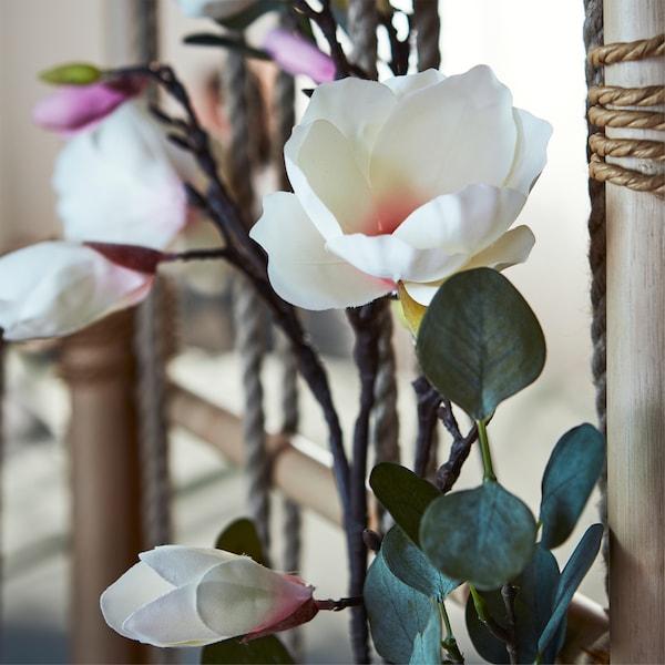 Teil eines TÄNKVÄRD Raumteilers, geschmückt mit SMYCKA Kunstblumen und -blättern (mit Schnur befestigt).