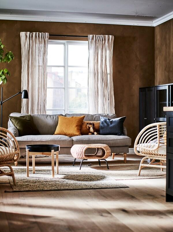 Teil eines Wohnzimmers, das in satten Naturfarben gestrichen und eingerichtet ist, u. a. mit Aufbewahrung, Sitzgelegenheiten, Beistelltischen und einem GAMLEHULT Hocker.
