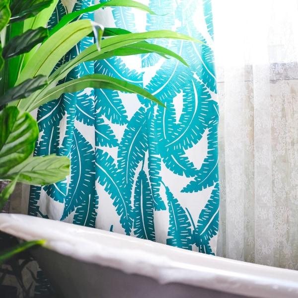 Tejido estampado blanco y turquesa usado como cortina de ducha rodeando una bañera blanca. Hay una planta junto a la bañera.
