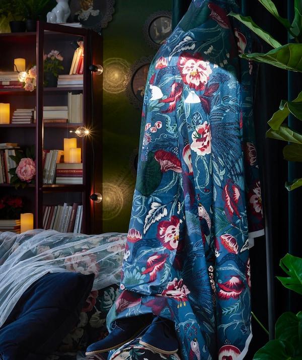 Tela con estampado floral cubriendo una lámpara de pie para crear un efecto fantasmagórico.