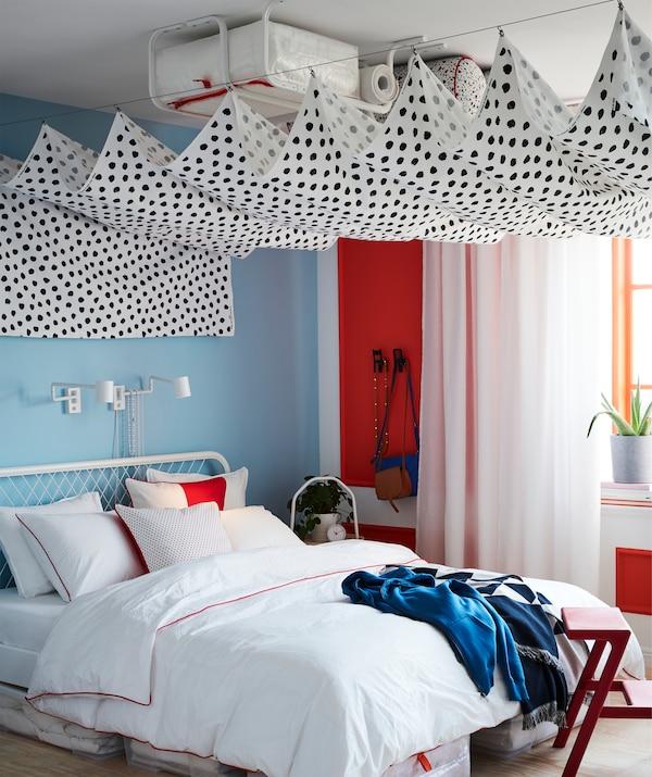 Tela SKÄGGÖRT colgada entre dos cables de cortina que ocultan varias barras para ropa instaladas en el techo de un dormitorio.