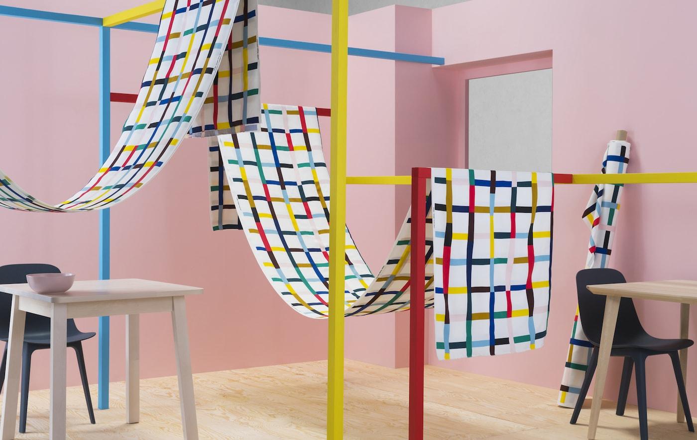 Telas con estampado multicolor colgadas en estructuras coloridas en una habitación rosa.