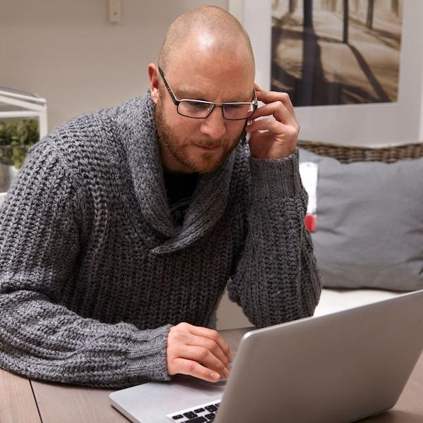 Telefonujúci muž, ktorý sedí za stolom s počítačom