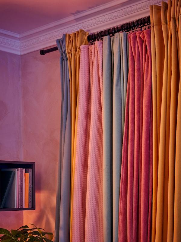Tende appese a un bastone arricchite con tessuti fissati agli anelli per tende SYRLIG a formare una grande tenda, colorata e continua - IKEA